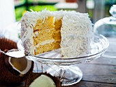 A sliced coconut cake on a cake stand