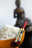 A bowl of rice and chopsticks in front of a statue of Buddha