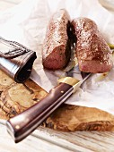 Saddle of venison with a knife on a wooden board