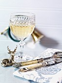A glass of white wine, cutlery and a napkin