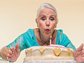 An old lady blowing out candles on a birthday cake