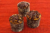 Pumpkin muffins decorated with chocolate spider webs for Halloween