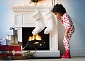 Little girl in front of festively decorated fireplace