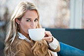 A blonde woman with a large cup of coffee