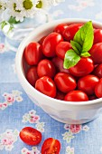 A bowl of fresh organic grape tomatoes with a sprig of basil