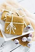 Quadratische Lebkuchenplätzchen mit Melasse und Ingwer, verziert mit Zuckergussschleifen