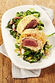 Saddle of venison wrapped in spicy bread dough on a savoy cabbage medley