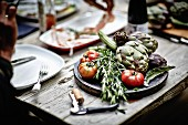 Artichokes, rosemary and tomatoes on a wooden board