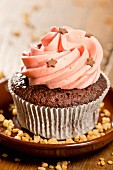 A chocolate cupcake decorated with pink cream