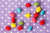Colourful sugar eggs on a spotted cloth (seen from above)