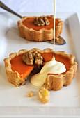 Vanilla sauce being poured over pumpkin pie