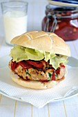 A chicken burger with roasted pepper relish on a ciabatta bun