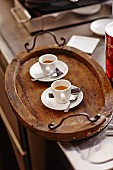 Two espressos on a wooden tray