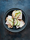 An open sandwich topped with turkey ham, Camembert and avocado