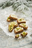 Christmas biscuits decorated with icing sugar and pistachios to look like open sandwiches