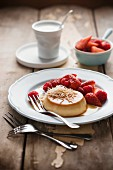 Creme caramel with coconut, strawberries and raspberries