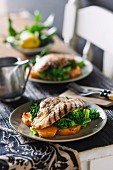 Grilled barramundi fillets on a bed of sweet potatoes and broccoli