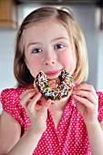 Kleines Mädchen isst Doughnut mit Zuckerstreuseln