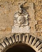 A historic coat of arms above an archway in the town of Pitigliano (Tuscany, Italy)