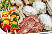 Beef steaks, baked potatoes, sausages and vegetable skewers ready for a barbecue