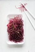 A bowl of red seaweed with chopsticks