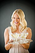 A woman holding a tray of champagne glasses