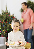 A boy holding a plate of Christmas biscuits
