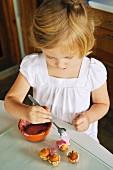 Kleines Mädchen verziert Minimuffins in der Küche