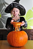 A girl in a Halloween costume with a pumpkin