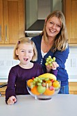 Mutter und Tochter mit Obstschale in der Küche
