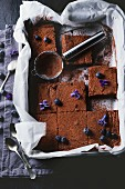 Sliced chocolate cake in a baking tray with blueberries and sugared violets