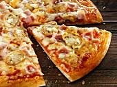 Pizza mit Schinken und Champignons, angeschnitten