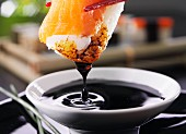 Sushi being dipped in soy sauce (close-up)