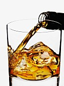 Whisky being poured into a glass over ice