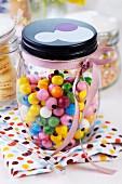 Vorratsglas mit bunten Kaugummikugeln und rosefarbenem Geschenkband verziert