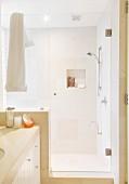 Modernes Bad, abgetrennter Duschbereich mit Glastür, sandfarbene Fliesen an Wand