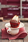 A chocolate muffin decorated with a pear