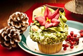 Vanilla cupcake decorated with pistachios and a flower for Christmas