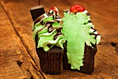 A chocolate cupcake decorated with mint cream, chocolate sauce and a cherry on a wooden table