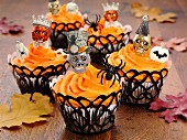 Halloween cupcakes on an oak table with autumnal leaves