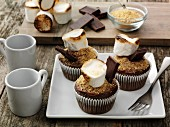 Chocolate cupcakes decorated with smores on a square plate