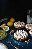 Lemon meringue pies, fresh lemons, icing sugar and a spoon