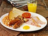 Englisches Frühstück mit Würstchen, Bacon, Spiegelei, Baked Beans und Toast