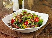 A colourful salad with beef steak