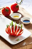 A fan-cut tomato filled with mozzarella and basil with balsamic vinegar and olive oil in the background
