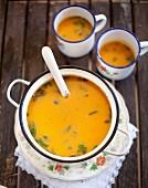 Sweet potato soup with ginger in an enamel pot with two cups of soup in the background