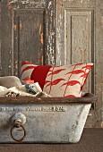 Rot-weiss gemustertes Kissen in Vintage-Metallwanne vor rustikaler Holztür mit abblätternder Farbe