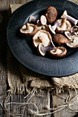 Purple wood blewits and shiitake mushrooms on a plate
