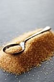 A teaspoon laying on a pile of brown sugar