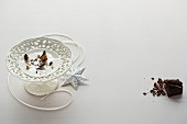 Crumbs on a white cake stand, a ribbon and a silver decorative star with grated chocolate to the left